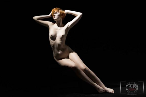 A young, nude woman, stretched out in blackness.