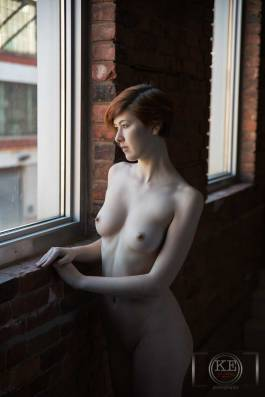 A young, nude woman, gazing out of a window.